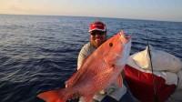 Captain Travis Palladeno catches a red snapper while saltwater fishing 120 miles off the coast of Florida