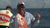 Chad Kinney catches a red snapper while saltwater fishing offshore out of Texas